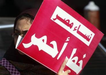 "A woman holds a sign that reads ""Egypt women red line"" as they protest against military council violations and virginity tests against females outside the State Council court and in support of Samira Ibrahim in Cairo, December 27, 2011. REUTERS/Amr Abdallah Dalsh"